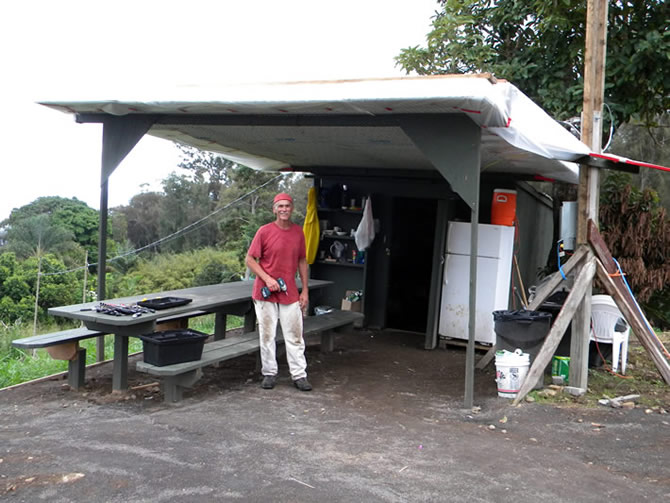Beau Flack standing under newly installed Tridipanel roof in front of the job shack, we placed visqueen over the Tridipanels to help keep our lunch area dry, also we purchased a use refrigerator Beau also built our lunch table.