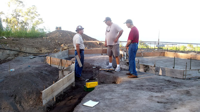 Mike Hess speaking to Rod Hadrian Sr. and engineer Ty Drake, Mike is checking the soil compaction prior to pouring the cement slab, all compaction-testing needs to be complete prior to the rebar placement.