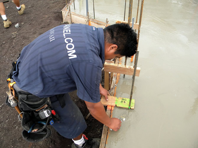 Julio placing rebar into freshly poured concrete, Julio has a pre-made template, you can see the two notches cut into the template, one for the outside bar and one for the inside bar, there is a cleat or stop on the bottom which fits against the form so each rebar is exactly the same distance from the edge and help line up the panels.